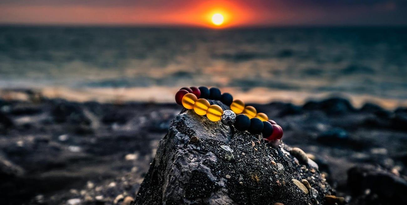 image d'un bracelet sur un caillou au bord de la mer